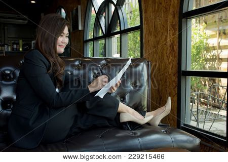 Happy Asian Businesswoman Write Work On Paper While Sitting On The Sofa In The Coffee Shop