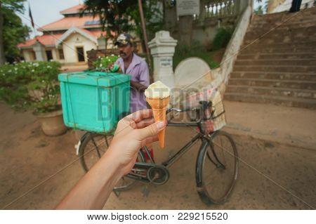 Dikwella, Sri Lanka - Dec 30, 2017: Hand With Sweet Ice Cream On The Street And Trader Of Desserts O