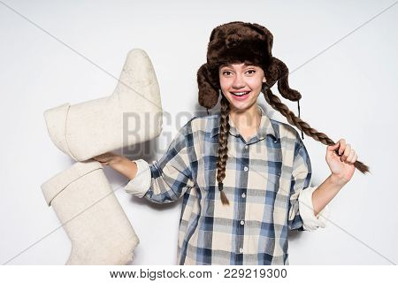 Happy Young Russian Girl In Warm Fur Hat Holds Winter Gray Felt Boots