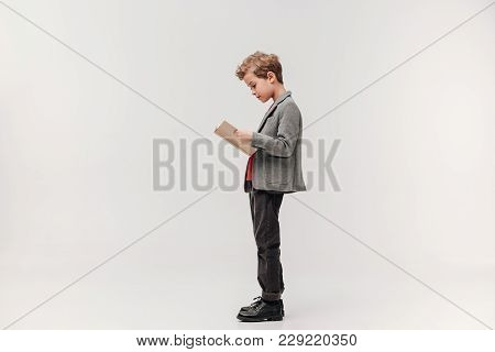 Side View Of Stylish Little Schoolboy Reading Book Isolated On Grey