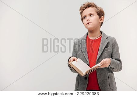 Bored Little Schoolboy Holding Book Isolated On Grey