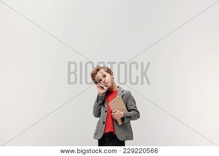 Stylish Little Schoolboy Talking By Phone While Holding Book Isolated On Grey