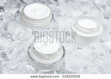 Cooling Effect Skin Care Products Concept. Glass Jars Of Cream Surrounded By Ice Cubes