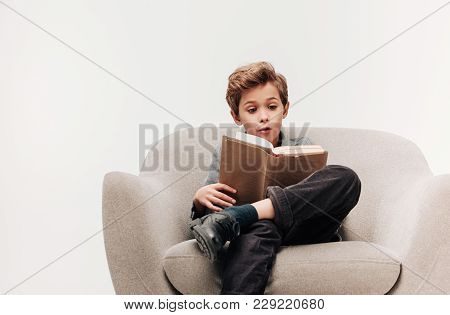 Excited Little Schoolboy Reading Book In Armchair Isolated On Grey