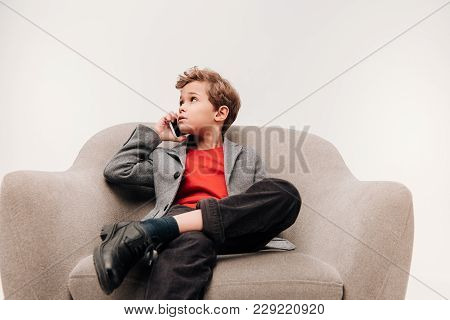 Stylish Little Boy Talking By Phone While Sitting In Comfy Armchair Isolated On Grey