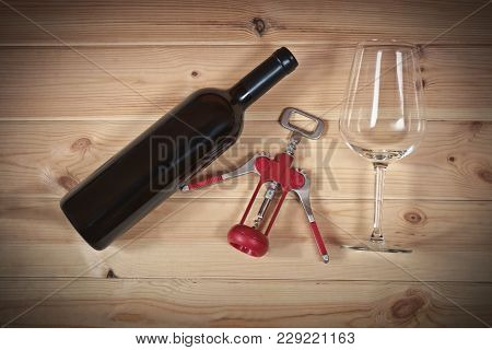 Red Wine Bottle, Empty Wine Glass And Corkscrew On Wooden  Background