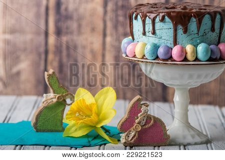 Blue Frosted Cake With Chocolate Drip Frosting And Easter Eggs In A Rustic Setting
