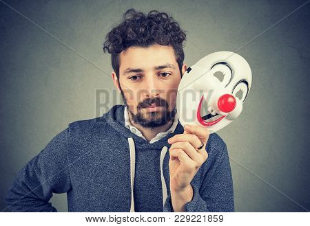 Young Bearded Upset Man Covering Personality With Happy Clown Mask On Gray Background.