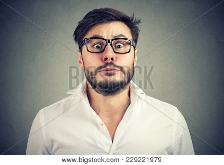 Young Bearded Man In Glasses Looking At Camera With Expression Of Panic On Gray Background.