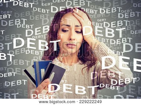 Concerned Woman Looking At Many Credit Cards Scared With Huge Amount Of Debt.