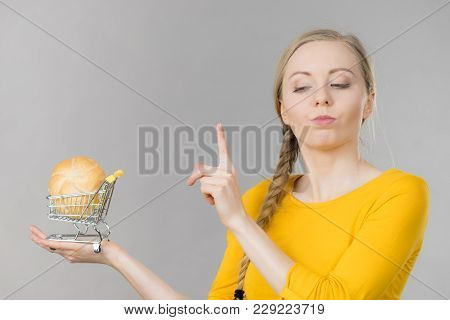Buying Gluten Food Products Concept. Skeptical Woman Holding Shopping Cart Trolley With Bun Breal Ro