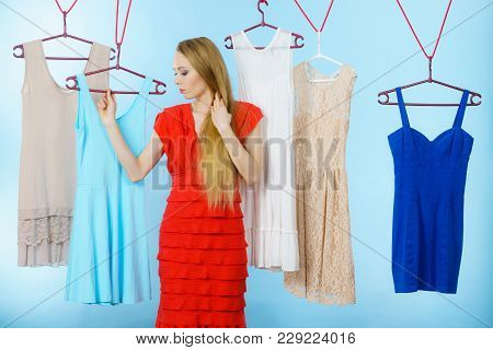 Young Blonde Long Hair Woman In Clothes Shop Store Picking Summer Outfit, Dresses Hanging On Clothin