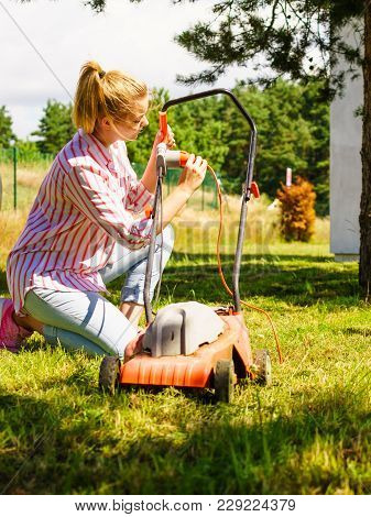Gardening. Female Person Being Mowing Green Lawn With Lawnmower, In Sunny Day.