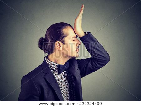 Young Elegant Man Slapping Forehead Upset With Foolish Mistake While Posing On Gray.