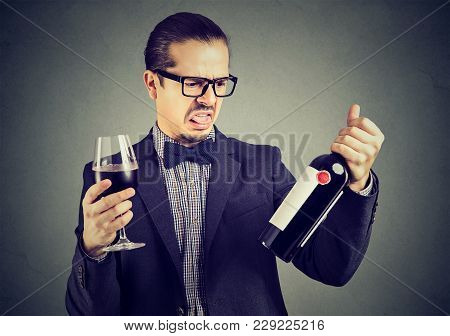 Young Formal Man Looking Grumpy While Tasting Red Wine And Exploring Bottle.