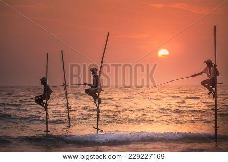 Mirissa, Sri Lanka - 18 January, 2018: Silhouette Of Fisherman Catching Fish At Sea At Sunset