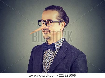 Business Man With Long Nose Isolated On Gray Background. Liar Concept. Human Emotions, Feelings.