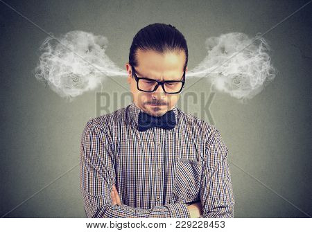 Young Man In Eyeglasses Driven Into Frenzy Looking Angry While Closing Eyes And Blowing Off Steam.