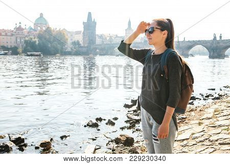 A Beautiful Young Tourist Girl With A Backpack Stands Next To The River Vltava In Prague And Admires