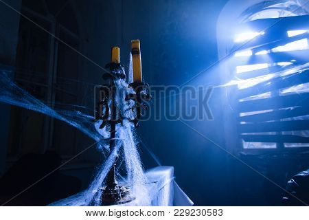 Old Candlestick With A Lot Of Spider Web. Blue Beam Of Light Through Window