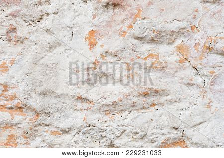 Textured Grunge Background. Volumetric Plastered Wall With A Multilayer Cracked Coating. Orange Chip