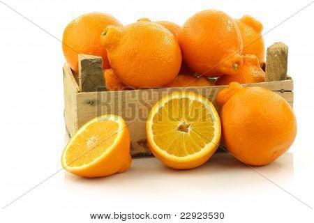 fresh and colorful  Minneola tangelo fruit and a cut one in a wooden crate