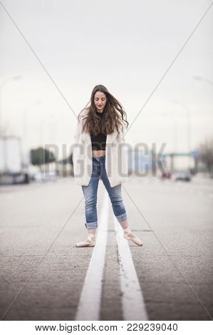 Woman Dancer With Ballet Tips, Jeans And White Coat On The Street And Look Down Vertical Format