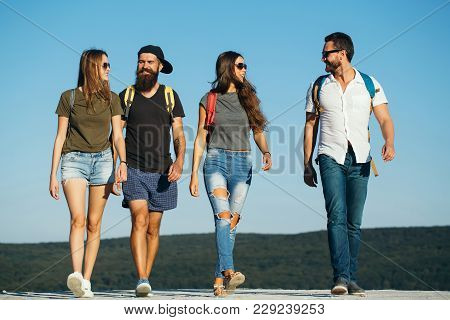Wanderlust, vacation, travel, hiking. Men and women travel on summer vacation. Happy friends on blue sky, wanderlust. Friendship, friends, young people, youth, relations. Fashion, style, lifestyle. poster