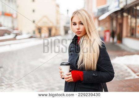 Pretty Glamorous Model Girl With Coffee In A Fashion Winter Vintage Coat With A Bag Walking In The C