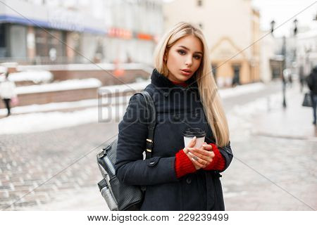 Stylish Beautiful Model Girl With A Cup Of Hot Coffee In A Fashion Coat With A Bag Walks In The City