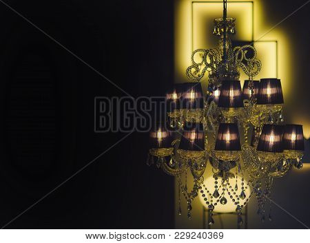 Expensive Chic Chandelier On Black Background. Chandelier With Warm Glowing In Dark Interior, Defocu