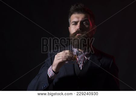 Man Or Businessman Drinks Wiskey On Black Background. Hipster With Beard And Mustache In Suit Drinks