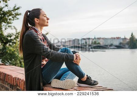 A Young Beautiful Girl On The Banks Of The Vltava River In Prague In The Czech Republic, Admires The