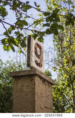 Poster With The Number 9 On Block Of Concrete With Trees Near