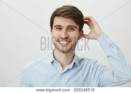Studio Portrait Of Hesitating Puzzled Attractive European Guy With Beard Scratching Head And Smiling