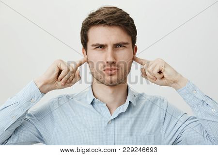 Annoyed Good-looking Man In Shirt Covering Ears With Index Fingers And Squinting With Serious Expres