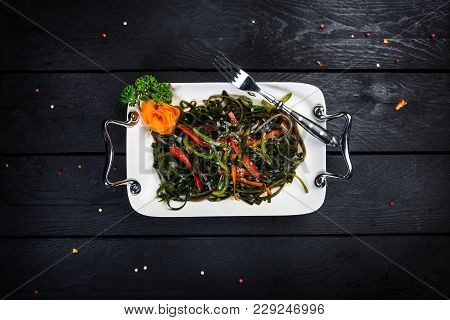 Chinese Salad With Sea Kale On The White Plate With Wooden Background, Top View
