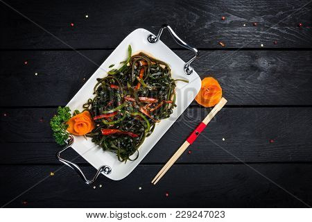 Chinese Salad With Sea Kale On The White Plate And Black Wooden Background, Top View