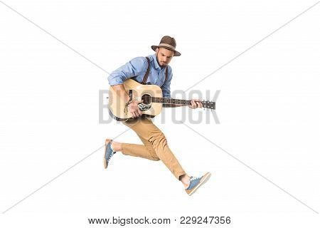 Handsome Young Man In Hat Playing Guitar And Jumping Isolated On White