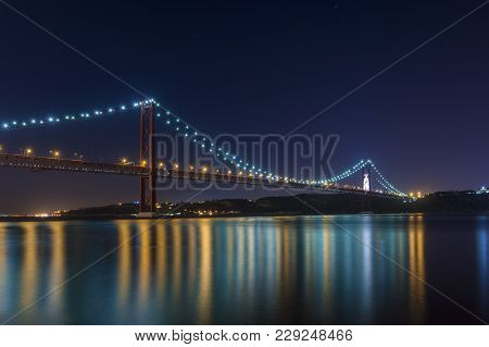 Beautiful And Serene View Of The Tagus River And The 25 Of April Bridge (ponte 25 De Abril) At Night