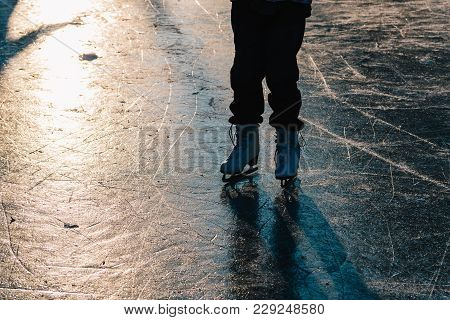 A Young Girl Standing In Skates On A Frozen Pond On Ice. Nice Soft Sunset Light. Detail Of Ice Skate