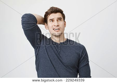 Pensive Dark-haired Man In Long-sleeved T-shirt Posing Against Gray Background, Frowns Face, Looks T