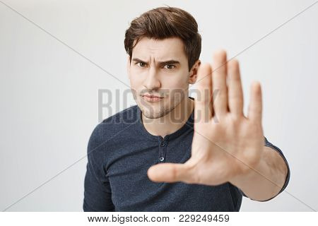 Serious Confident Angry European Man With Stubble Wearing Casual Clothes Posing Against Gray Studio