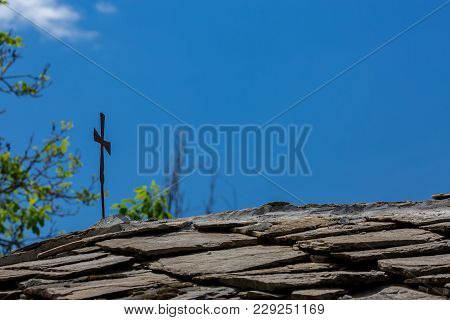 Vvery Old Vintage Metallic Cross On Traditional Stone Tiles Roof In Bulgaria