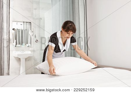 Housemaid Beating Pillows In Hotel Room. Portrait Of Nice Neat Lady Who Works As Maid Making Bed Whi