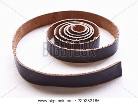Leather Belt Rolled With A Spiral On A White Background