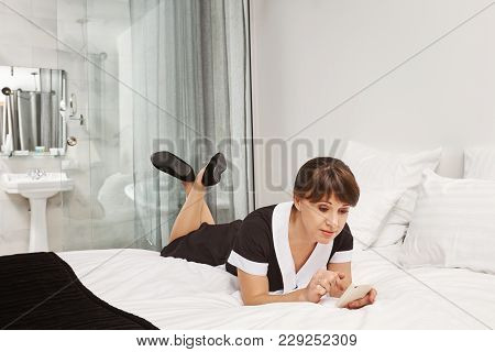 Nobody Will Notice That I Am Taking Break. Portrait Of Relaxed Housemaid Lying In Uniform On Bed, Br
