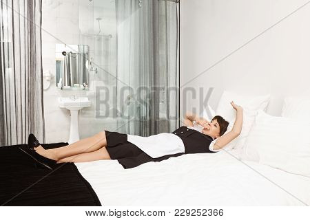 Maybe I Should Take Nap Before Clients Come. Shot Of Tired Woman In Maid Uniform Lying On Bed And Ya