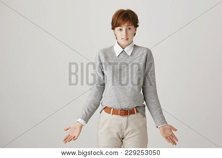 Embarrassed Good-looking Boyish Girl With Ginger Hair And Short Haircut, Biting Lip And Shrugging Wi