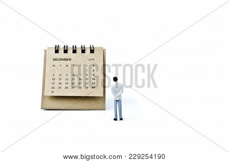 December. Two Thousand Eighteen Year Calendar And Miniature Plastic Man On White Background.
